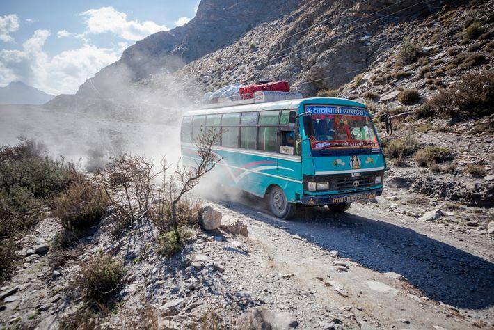 Un bus arpente la route poussiéreuse tracée le long de la rivière Kali Gandaki entre le ...