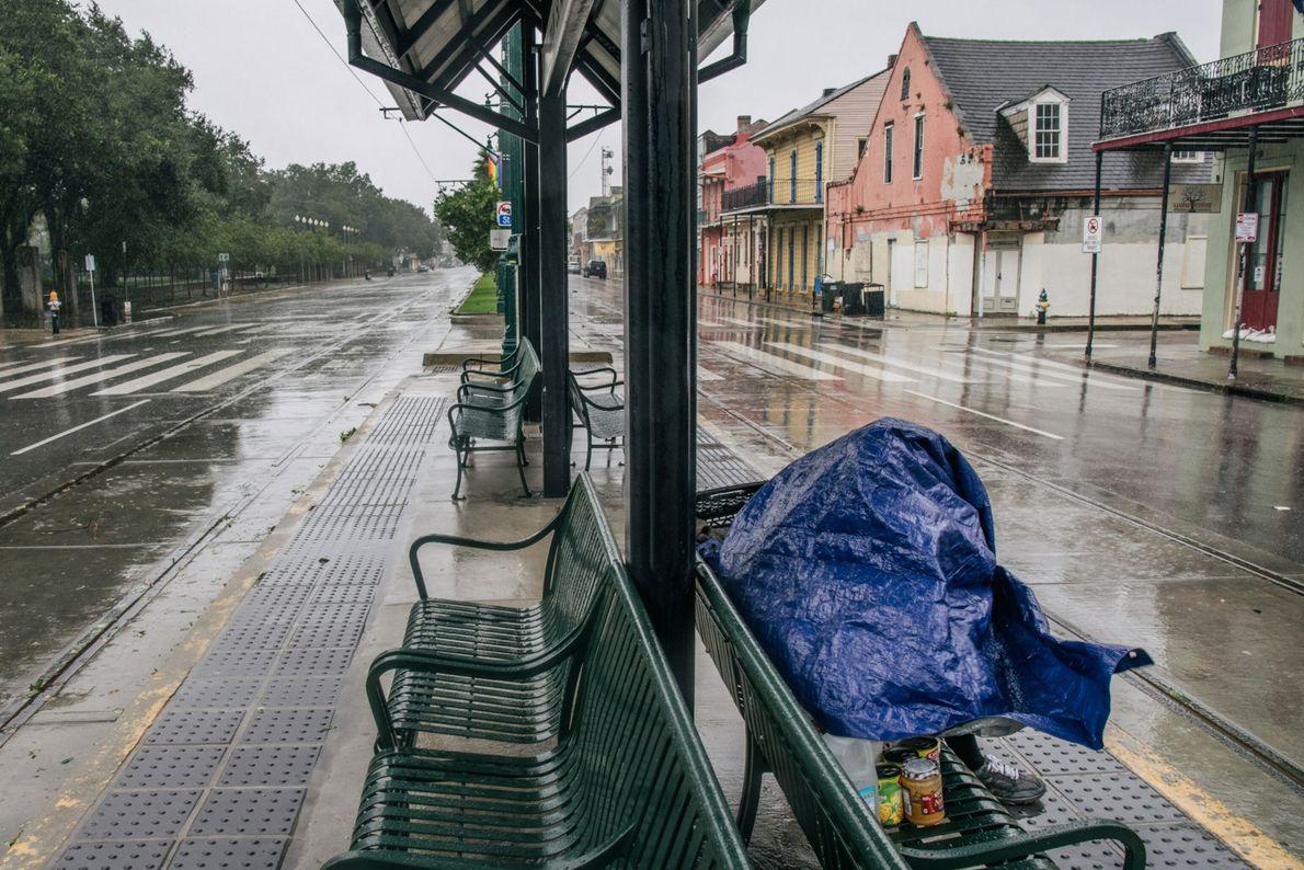 Un passant tente de s'abriter de la pluie sous un arrêt de bus alors que l'ouragan ...