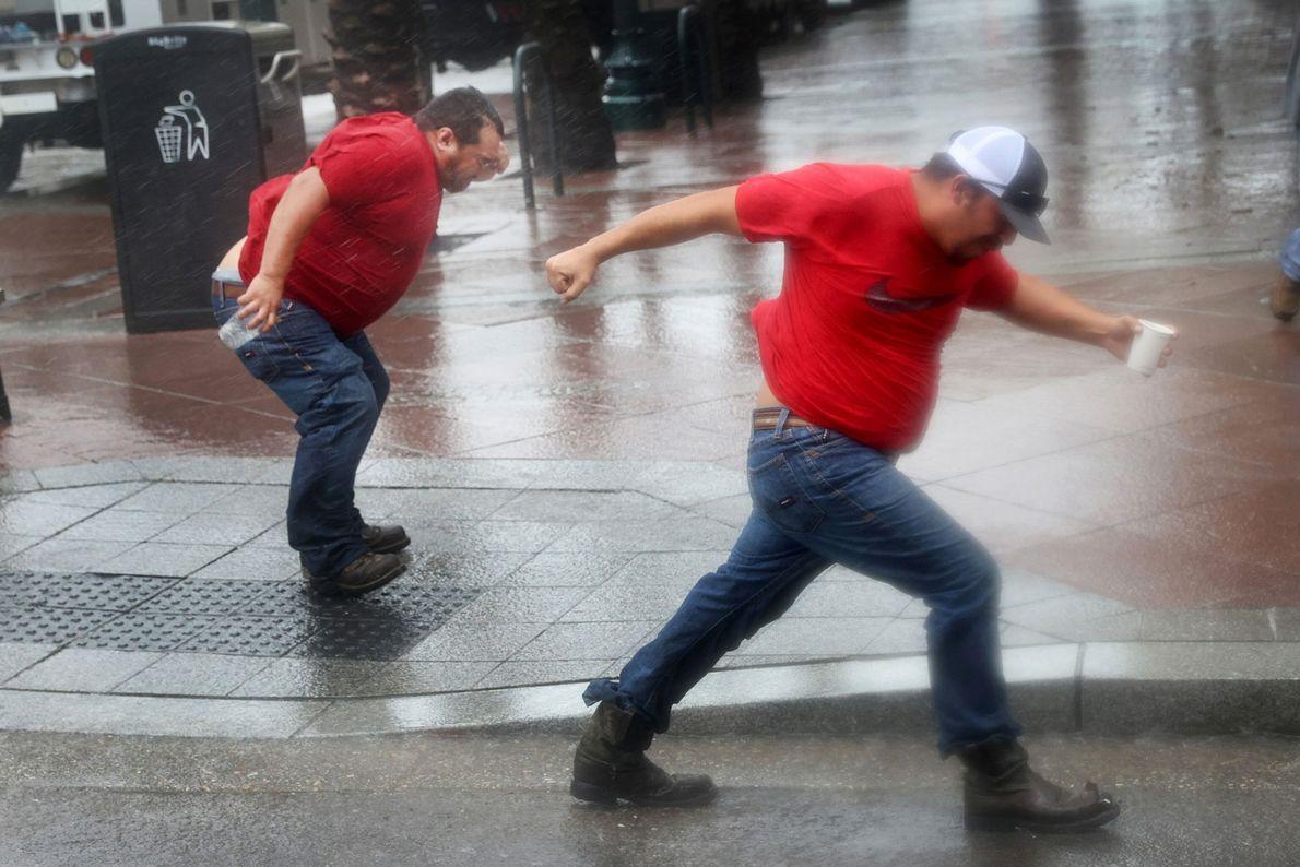 Des employés du service public luttent contre le vent de l'ouragan. Ils doivent attendre que les ...
