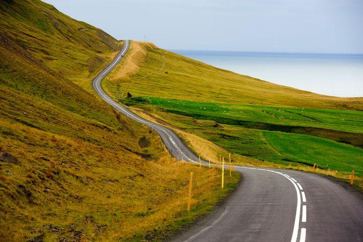 La route de l'Arctic Coast Way longe un fjord non loin du village de Siglufjörður. Les voies doubles ...