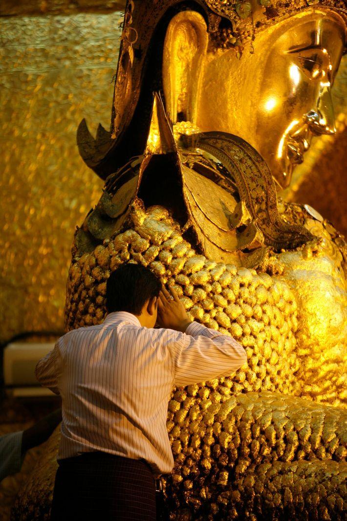 Des feuilles produites à l'atelier King Galon sont déposées sur cette statue de Bouddha haute de 4 m ...