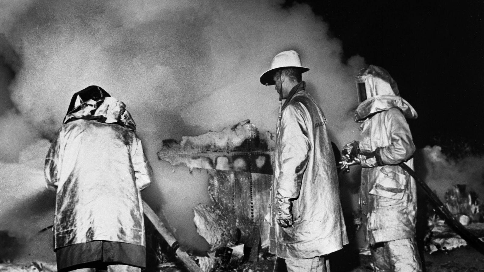 Des pompiers aspergent l'épave fumante d'un Boeing B-52 Stratofortress non loin de Faro, en Caroline du ...
