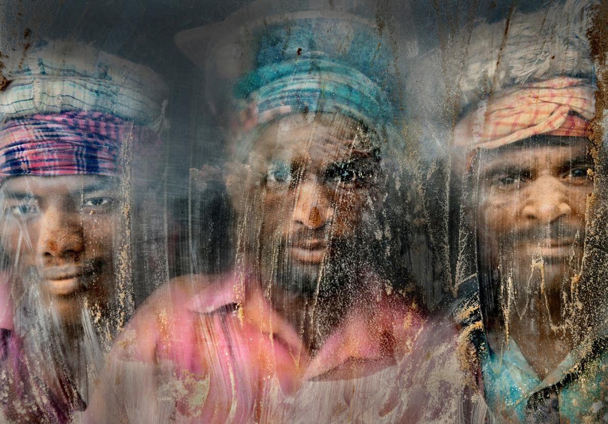 Trois ouvriers regardent à travers la vitre de leur poste de travail. Chittagong, Bangladesh.