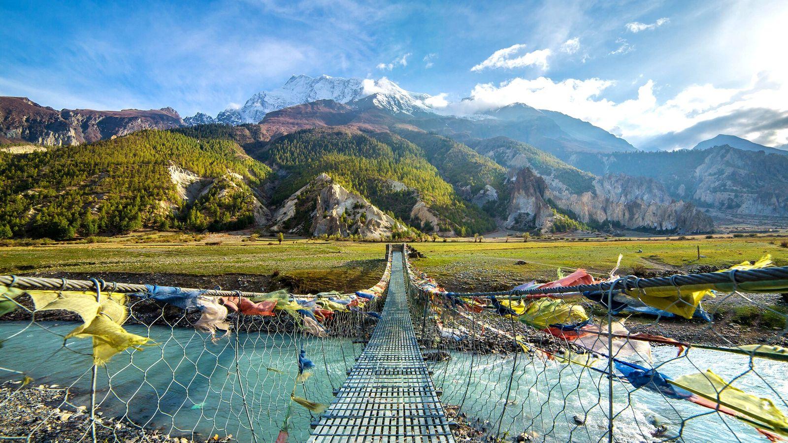 Ce pont décoré de drapeaux de prière enjambe une rivière du district de Mustang au Népal, une ...