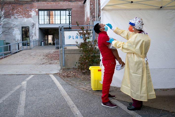 Un soignant teste un patient pour le coronavirus dans un centre de test de Providence, dans ...