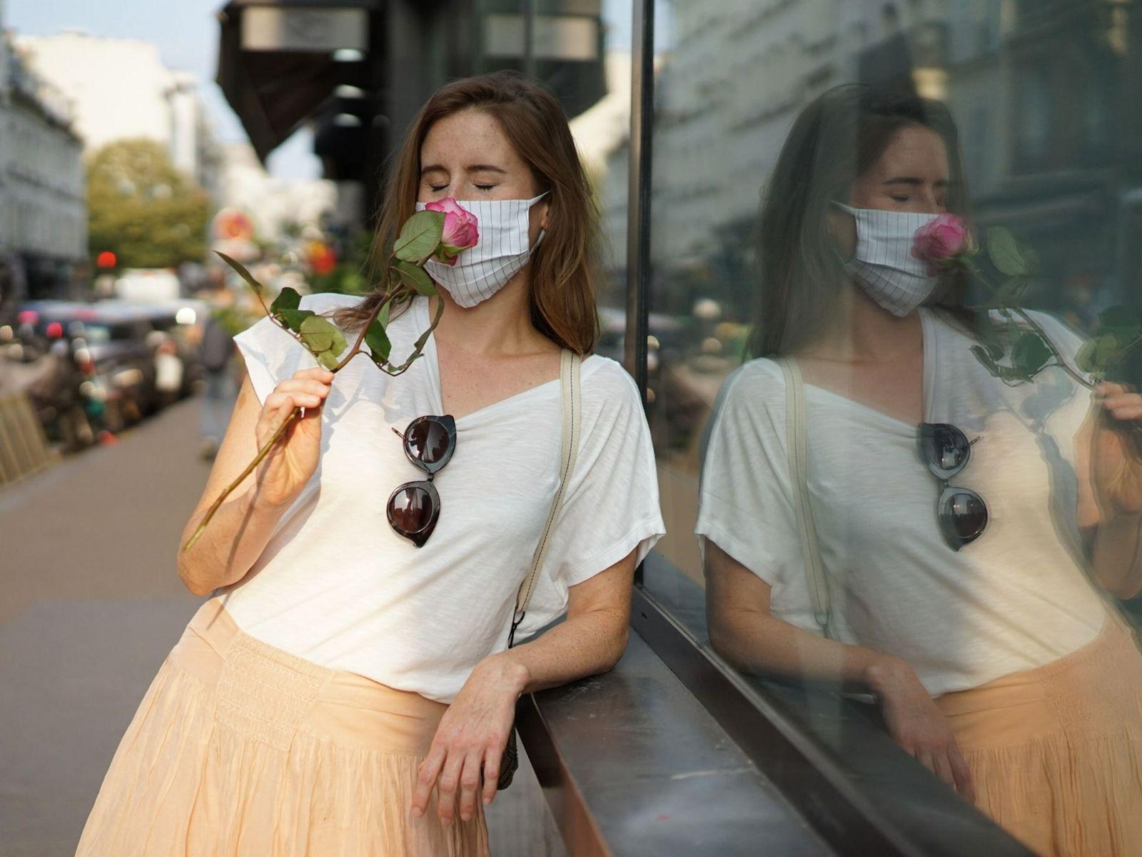 À travers son masque, une femme sent le parfum d'une rose au détour d'une promenade dans ...