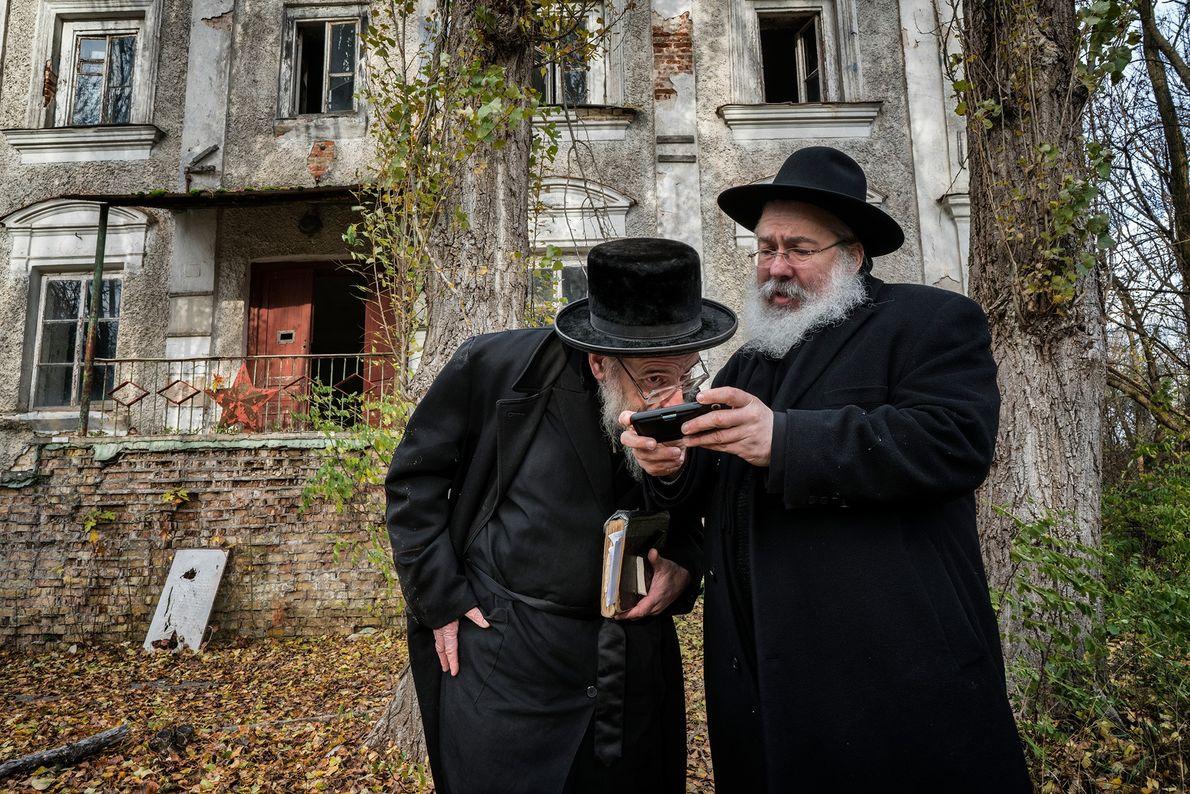 Devant l'ancienne synagogue, Yitz Twersky montre des images d'archives au rabbin Leibel Sirkes, qui a aidé ...