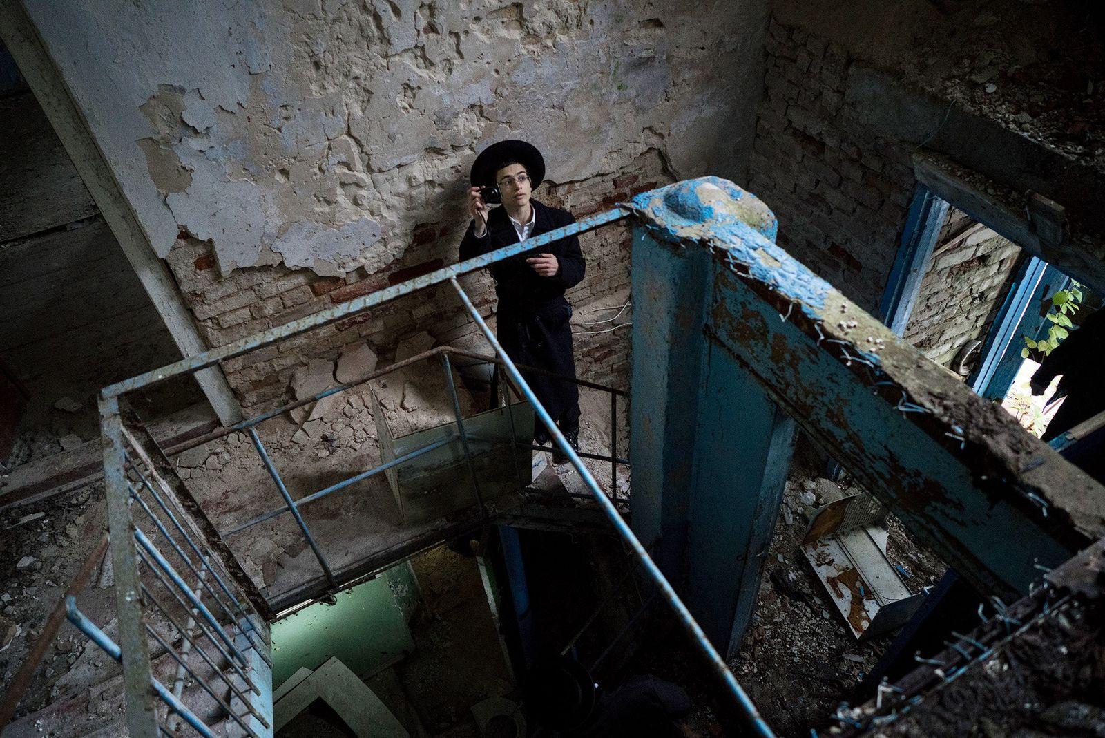 Un visiteur de la synagogue abandonnée de Tchernobyl fait une pause pour prendre une photo.