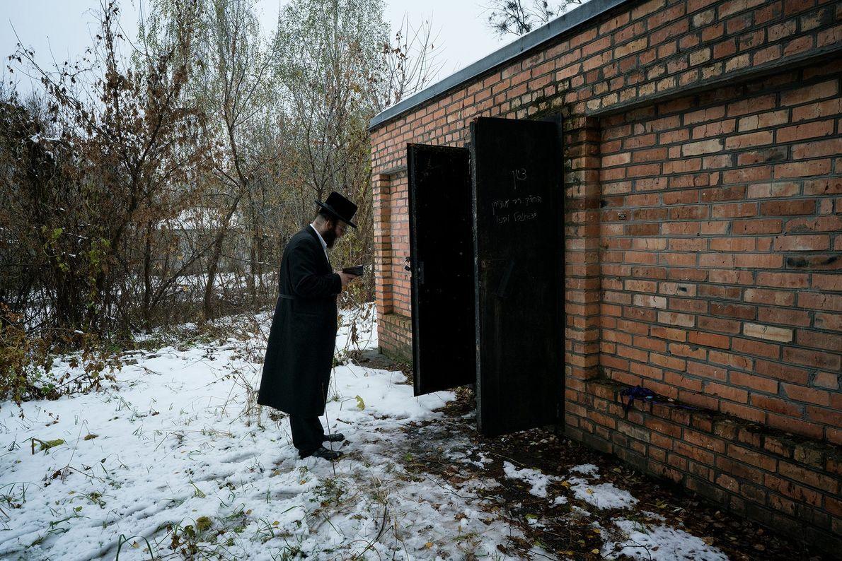 Un homme prie devant la tombe de Grand Rabbin Menachem Nachum Twersky, un disciple du fondateur ...