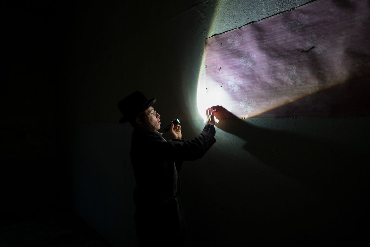 Un visiteur éclaire les murs de la synagogue abandonnée pour mieux les étudier.