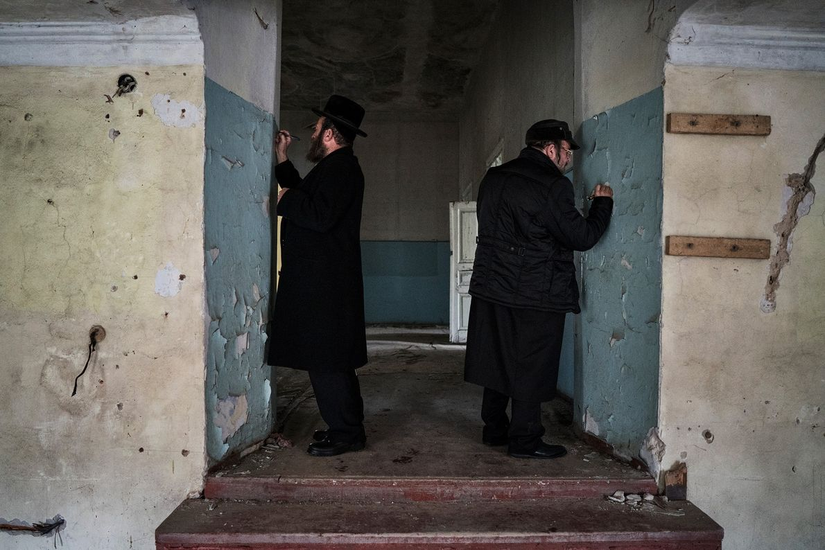 Après un long voyage, deux pèlerins écrivent leurs noms sur les murs de l'ancienne synagogue.