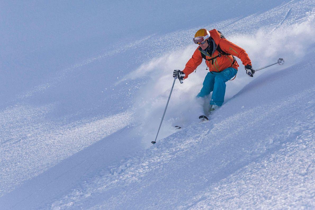 Sur la péninsule des Trolls, en Islande, un skieur projette de la poudreuse.
