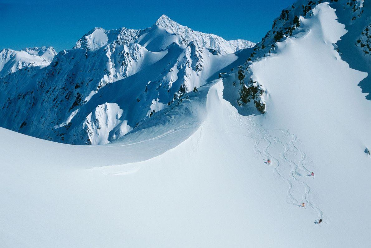 Dans la chaîne de montagnes Rakaia, dans les Alpes du Sud, en Nouvelle-Zélande, des héli-skieurs slaloment ...