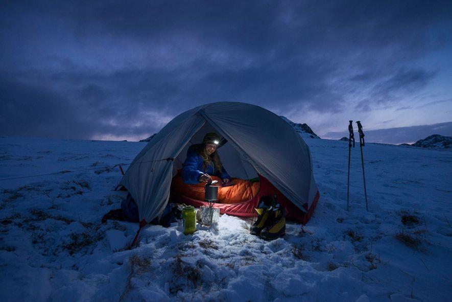Une femme prépare son petit déjeuner dans sa tente pendant une nuit de bivouac à Vestvågøya, ...