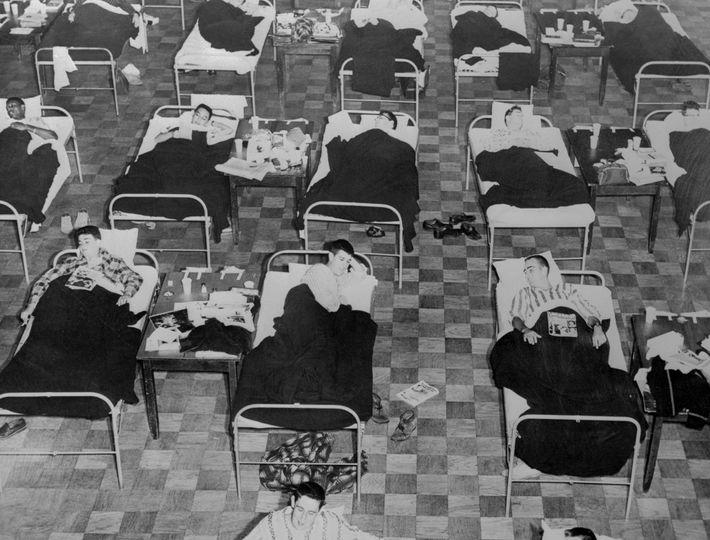 Contaminés par la «grippe asiatique» de 1957, ces étudiants sont tenus de s'allonger sur des lits ...