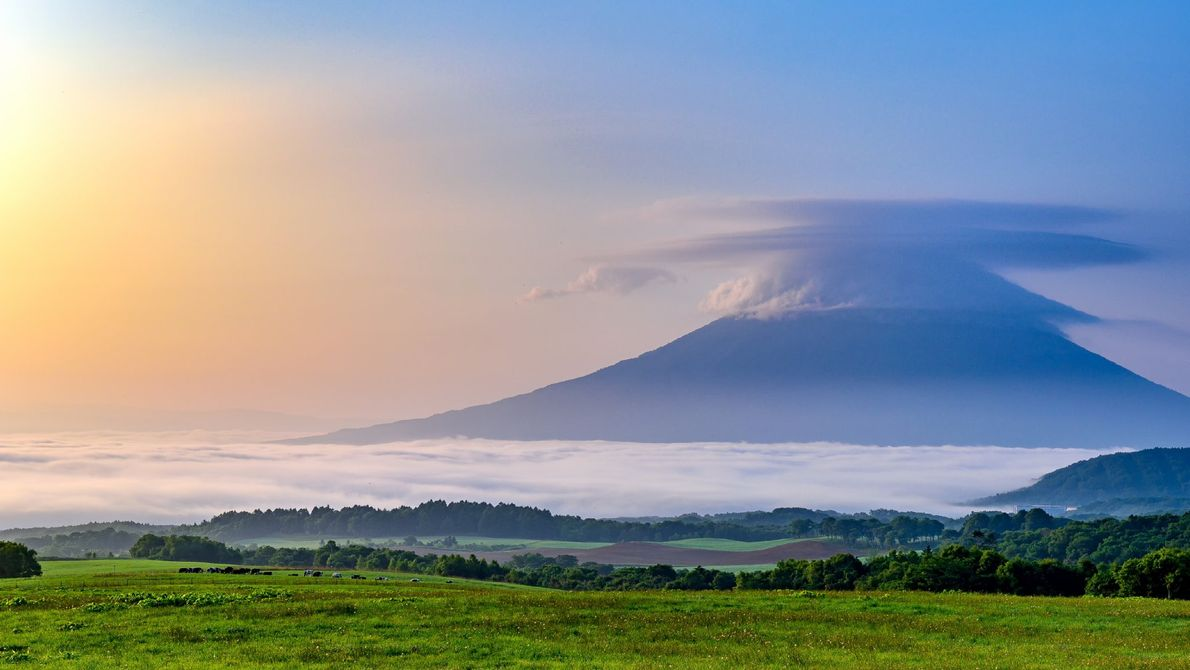 Surmonté d'un pileus et chaussé d'un épais brouillard, le mont Yōtei à Hokkaido, au Japon, se ...