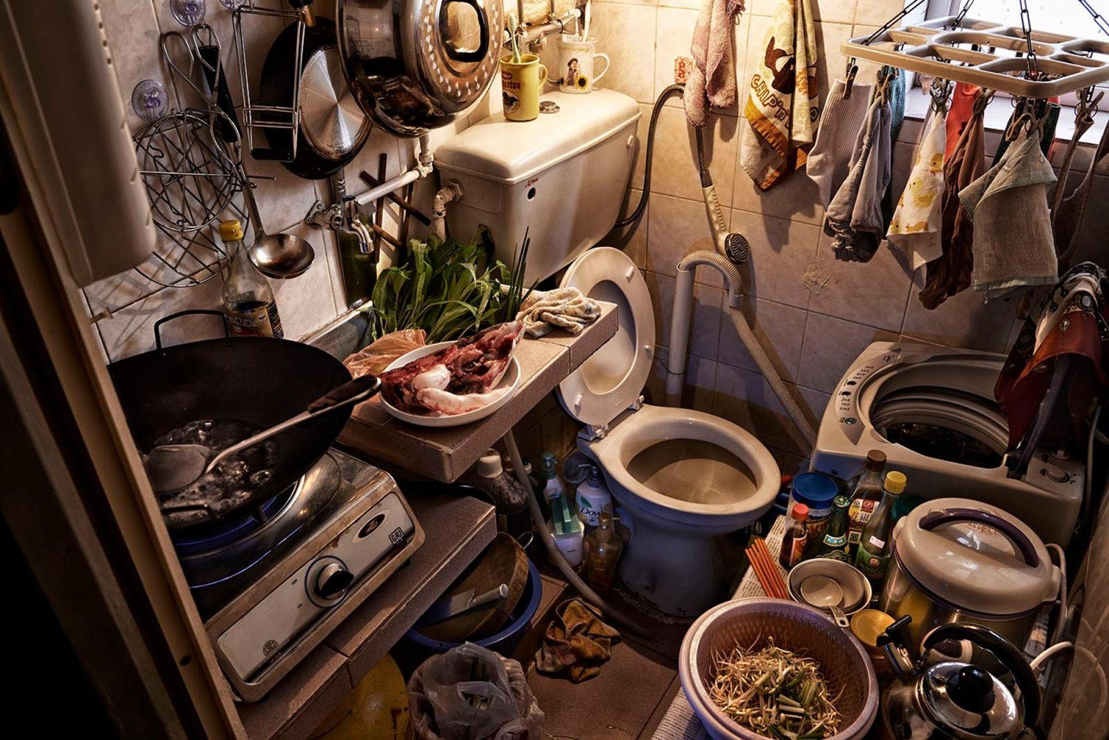 Une pièce réunissant toilettes et cuisine dans une maison-cage.