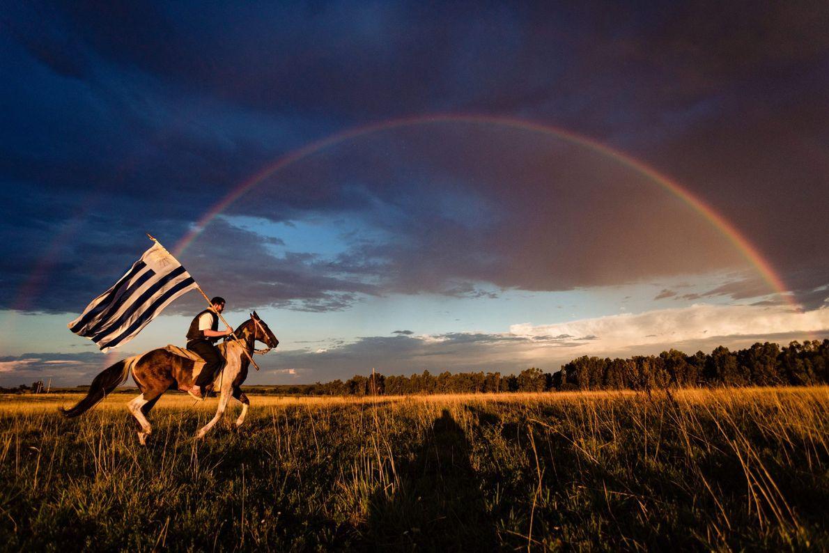 En Uruguay, un cavalier galope sous un arc-en-ciel en brandissant le drapeau bleu et blanc du ...