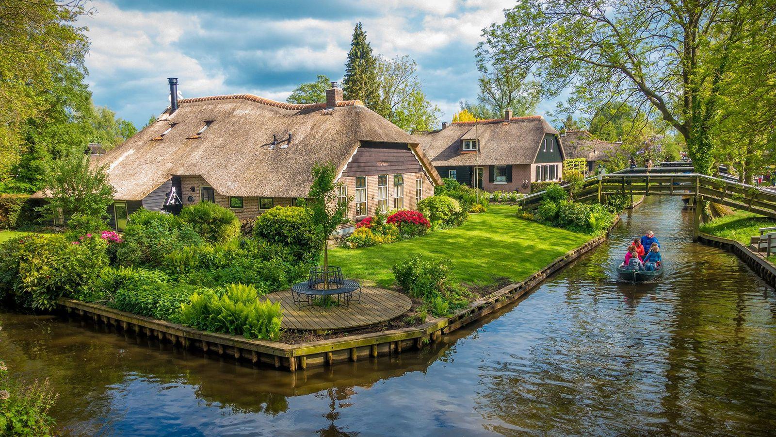 Une barque vogue sur un canal à Giethoorn, un village néerlandais érigé sur de petites îles ...