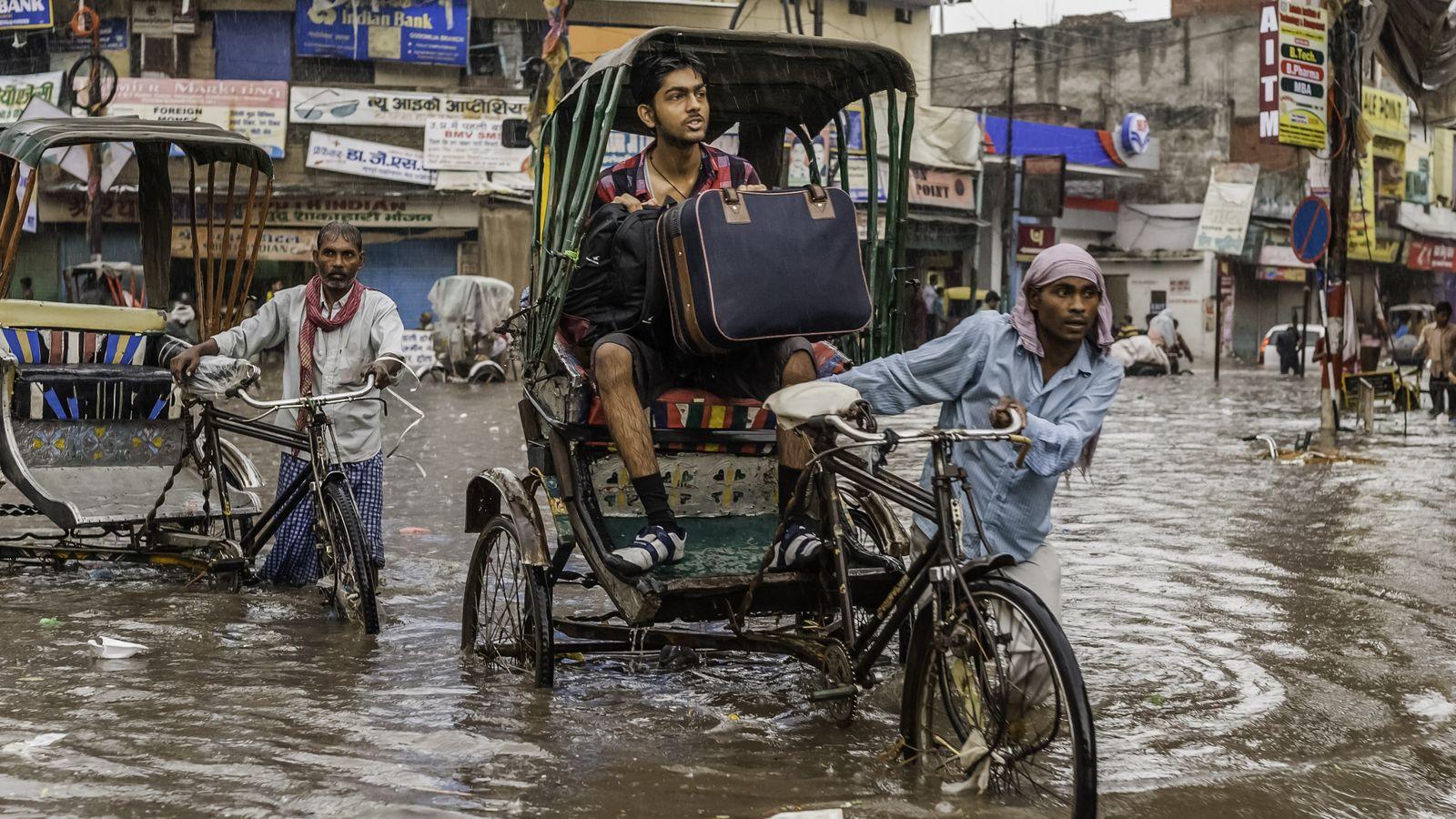 Varanasi, Inde - 11 août 2011: des rickshaws et un passager avec une valise tentent de ...