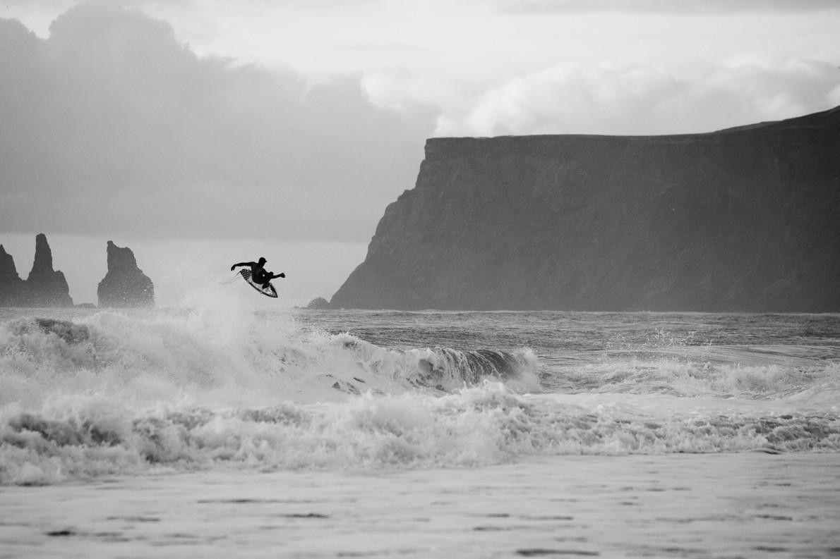 Un surfeur s'envole au dessus d'une vague en Islande. Même si ses eaux sont glacées, l'Islande ...