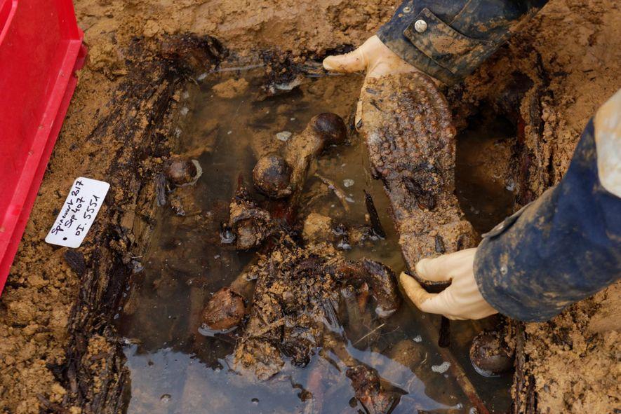 Prélèvement d'une chaussure de soldat dans l'un des ossuaires d'une importante fosse collective.