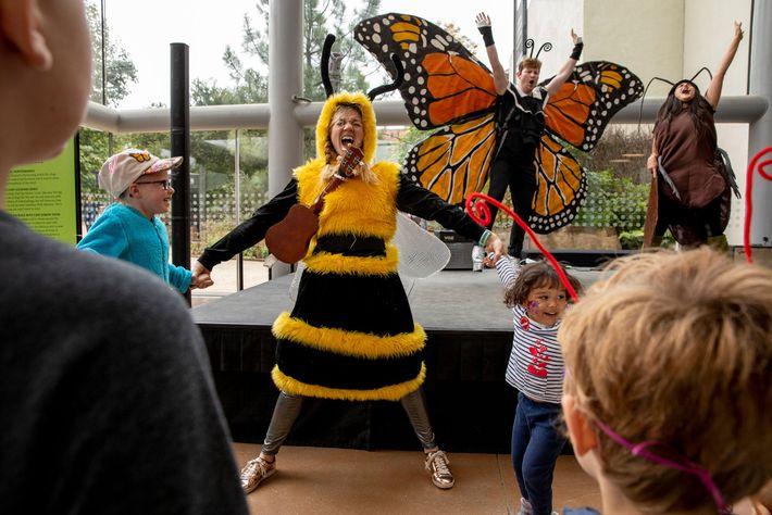 Des adultes déguisés en abeille, en papillon et en cafard jouent un spectacle pour enfants à ...