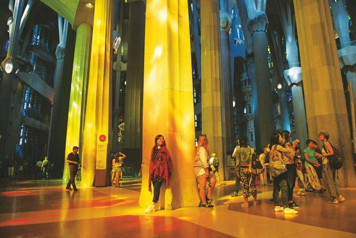 Les rayons du soleil filtrent à travers les vitraux, éclairant l'architecture aérienne de la Sagrada Família.