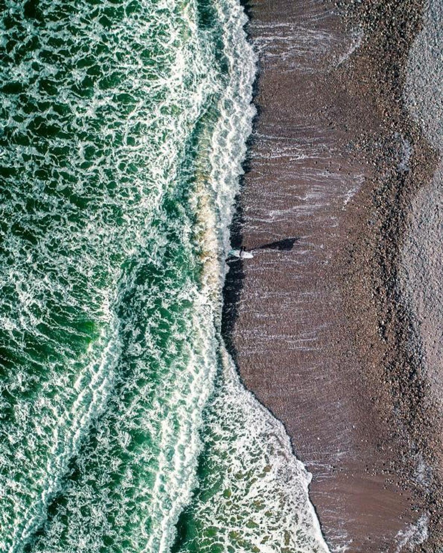 Près de la ville côtière de Tramore, un surfeur émerge de la mer d'Irlande glacée.