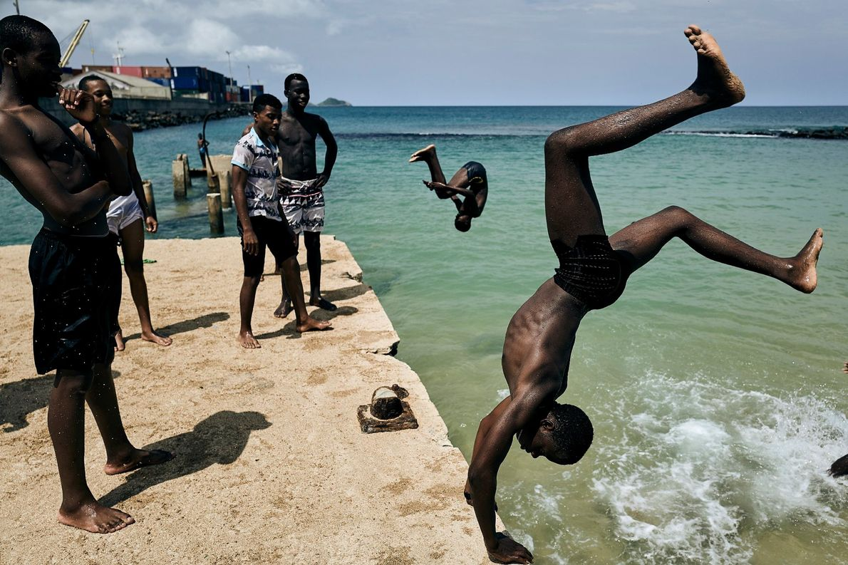 De jeunes baigneurs rivalisent d'imagination pour sauter dans les eaux du golfe de Guinée, sur l'île ...