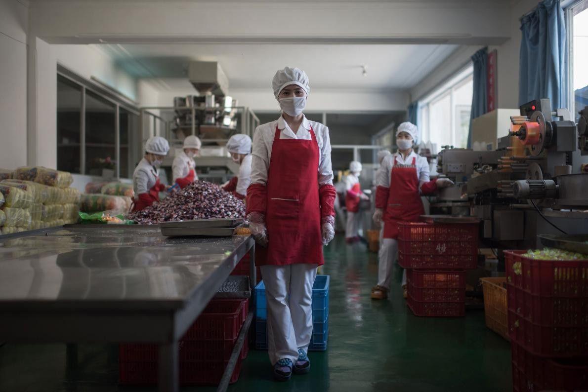 Hong Kum Ju, 27 ans, pose dans l'usine de transformation des aliments où elle travaille, près ...