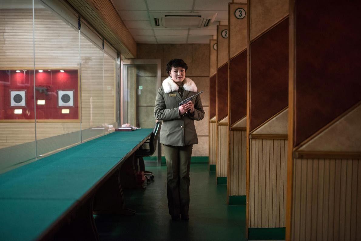 Kim Su Ryon, instructrice de tir nord-coréenne, pose avec un pistolet dans le stand de tir ...