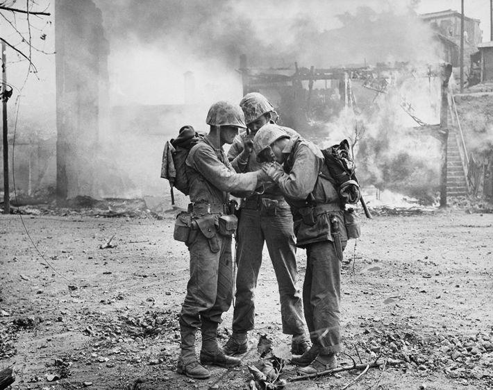Des soldats américains partagent une allumette pour allumer leurscigarettes au milieu de ruines fumantes à Séoul, ...