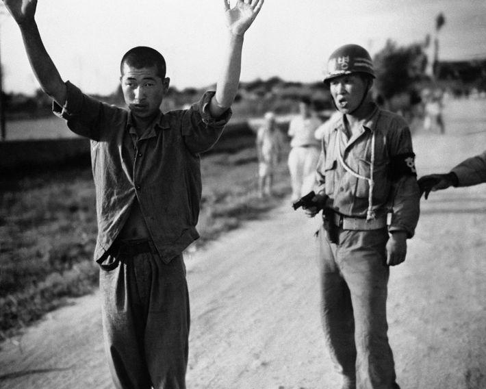 Un policier militaire sud-coréen accompagne un prisonnier de guerre nord-coréen vers une palissade en Corée du ...
