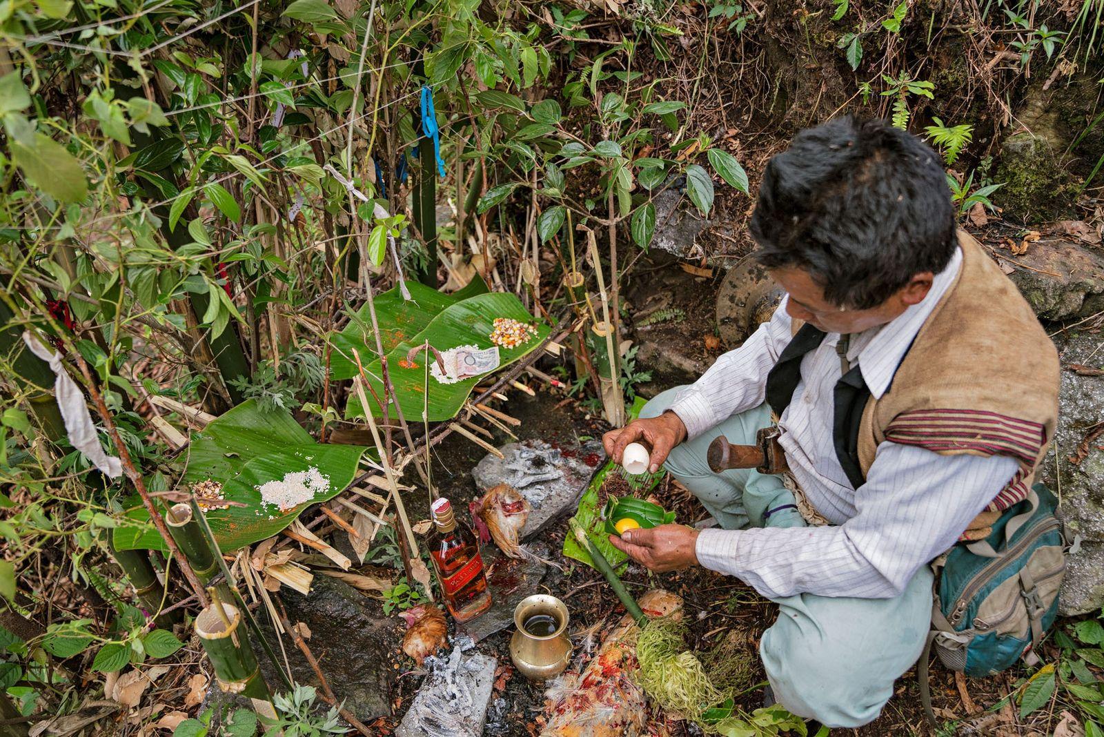 Le chaman casse un œuf devant deux autels en feuilles de bananier érigés pour honorer les ...