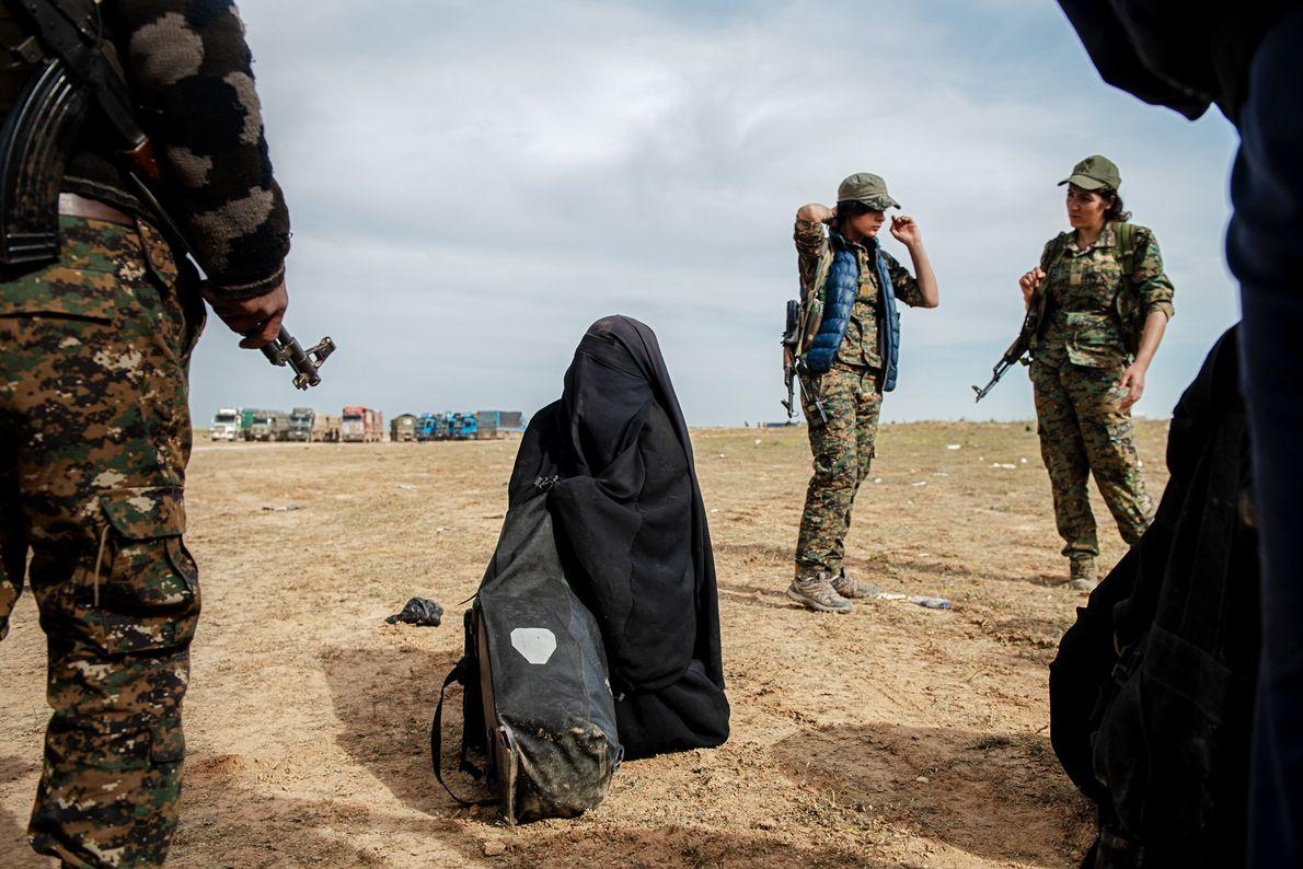 Des combattants kurdes encerclent une femme qui se rend alors que l'État islamique abandonne la ville ...