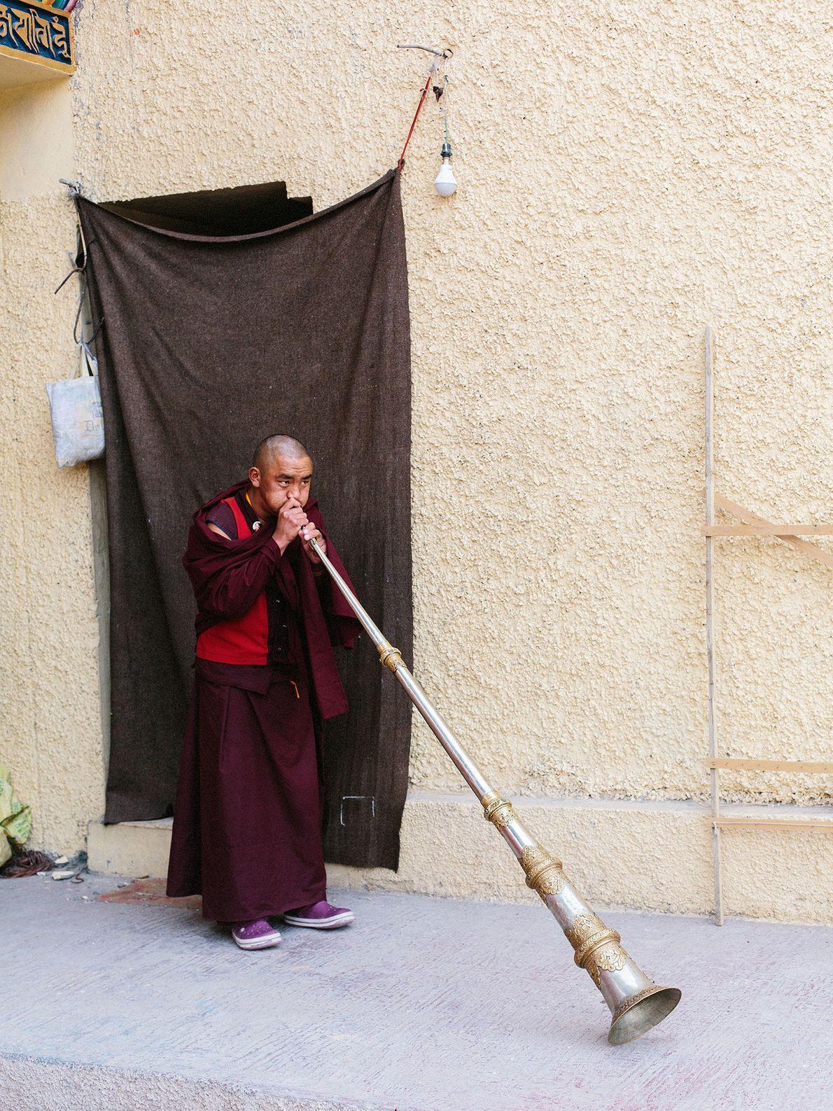 Dans le monastère Karma Dupgyud Choelingk, un jeune moine souffle dans une trompette cérémonielle, appelée dungchen.