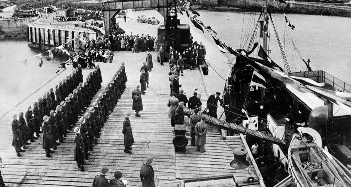 Les habitants d'Aurigny, évacués pendant la guerre, accueillis à leur retour sur l'île par les troupes ...