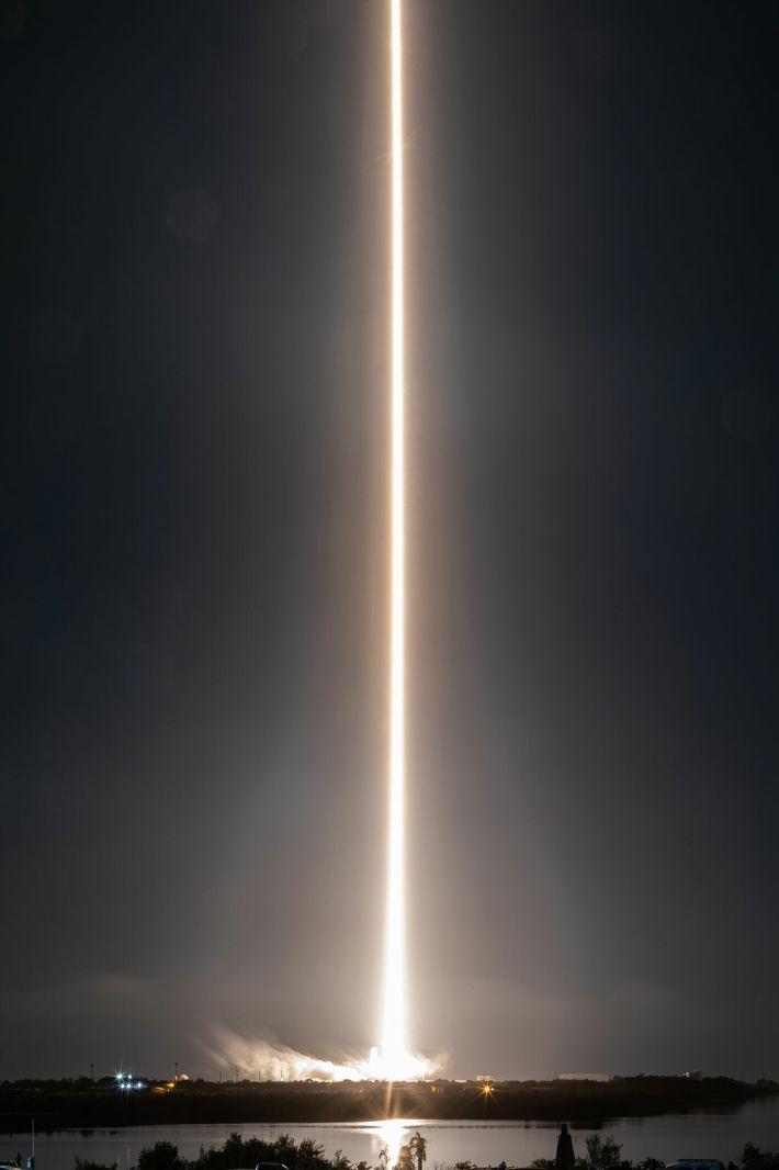 Ce cliché pris en exposition longue montre la traînée d'une fusée Falcon 9, qui transporte les membres ...