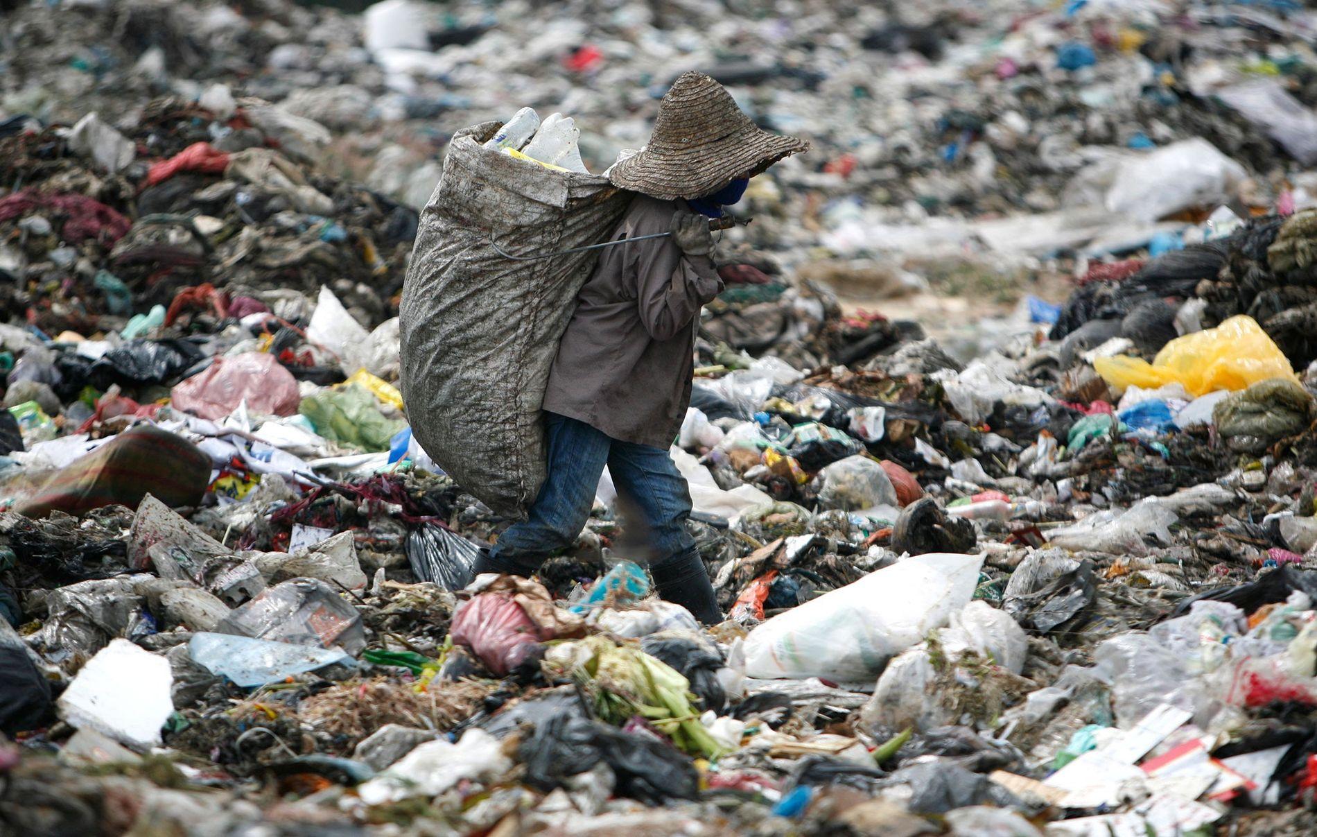 Un homme cherche du plastique à recycler dans une décharge en Malaisie.