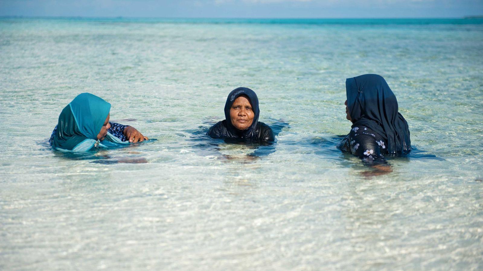 Après un pique-nique familial sur la plage, Aishath, Maryam et Zahira se rafraîchissent dans quelques centimètres ...