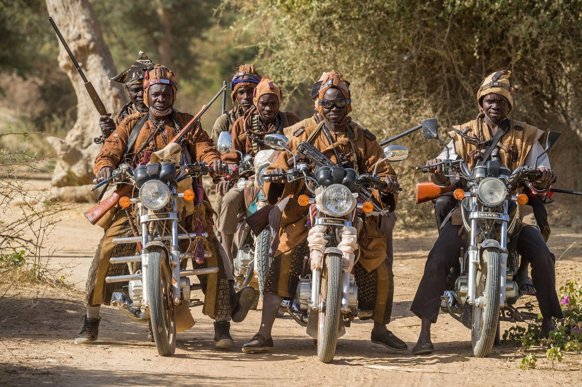 Les membres d'une société traditionnelle de chasseurs du Mali central se rassemblent sur leurs motos. Ces ...
