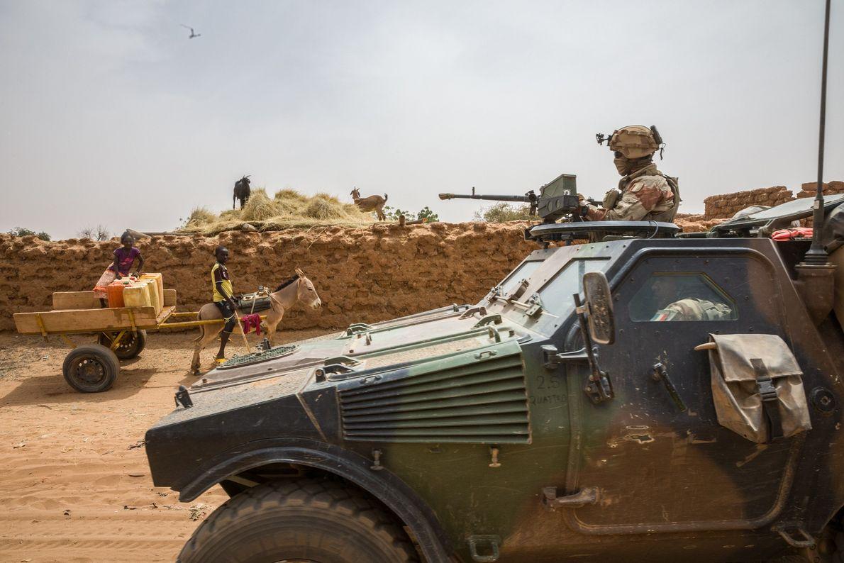 Un véhicule blindé français traverse le village d'Andéramboukane près du Niger. Les militants islamistes montent parfois ...