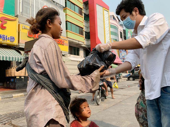 Aung Ko Ko, le directeur d'un hôtel de Mandalay, désormais vide, distribue de la nourriture aux ...