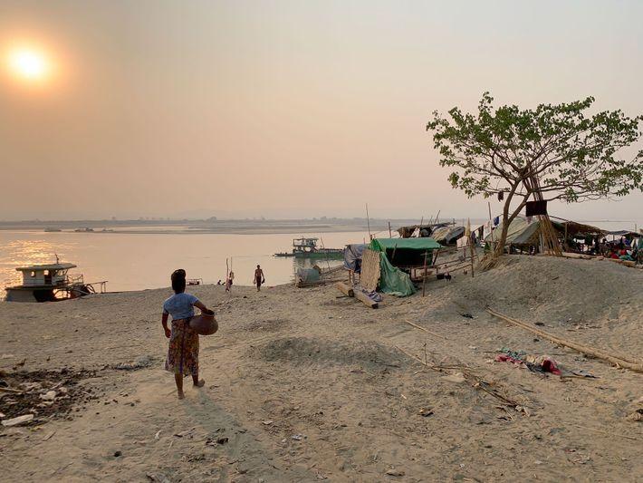 La célèbre rivière Irrawaddy passe devant Mandalay. Les journaliers qui déchargent les navires sont pour la plupart ...