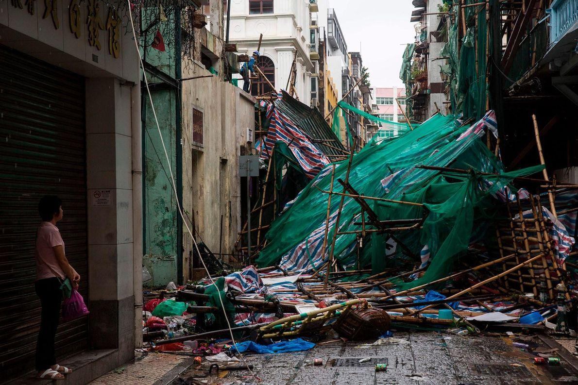 À Macau, dans le sud de la Chine, une femme observe un ouvrier qui démonte les ...
