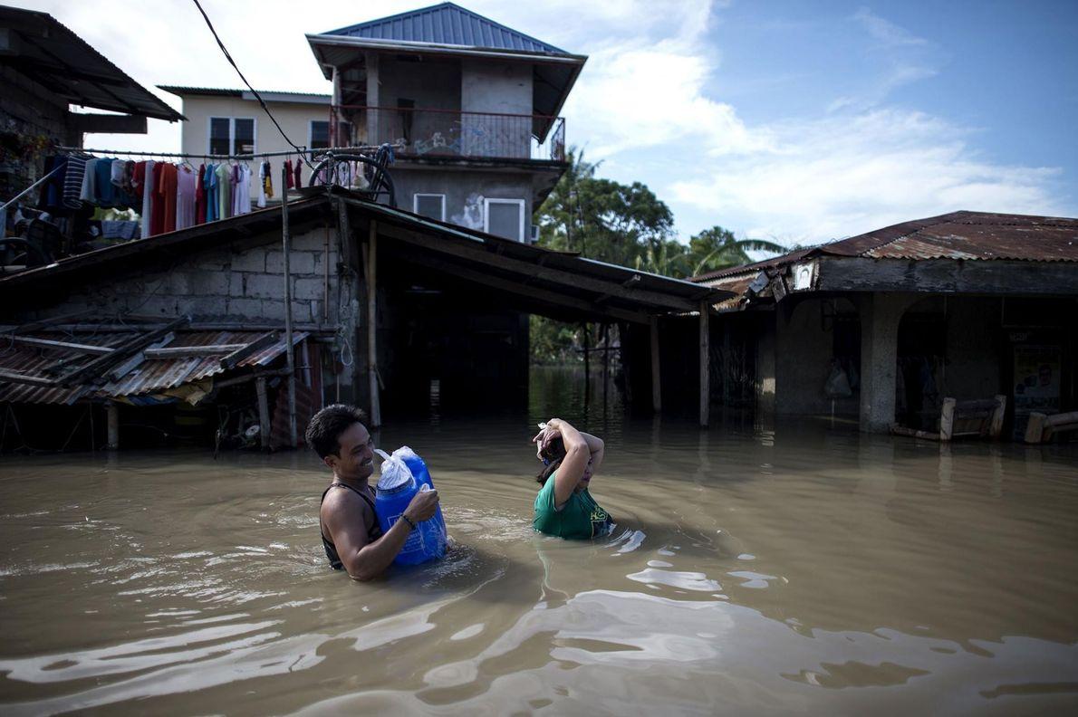 À Calumpit, dans la province de Bulacain, aux Philippines, des habitants pataugent dans les rues inondées. ...
