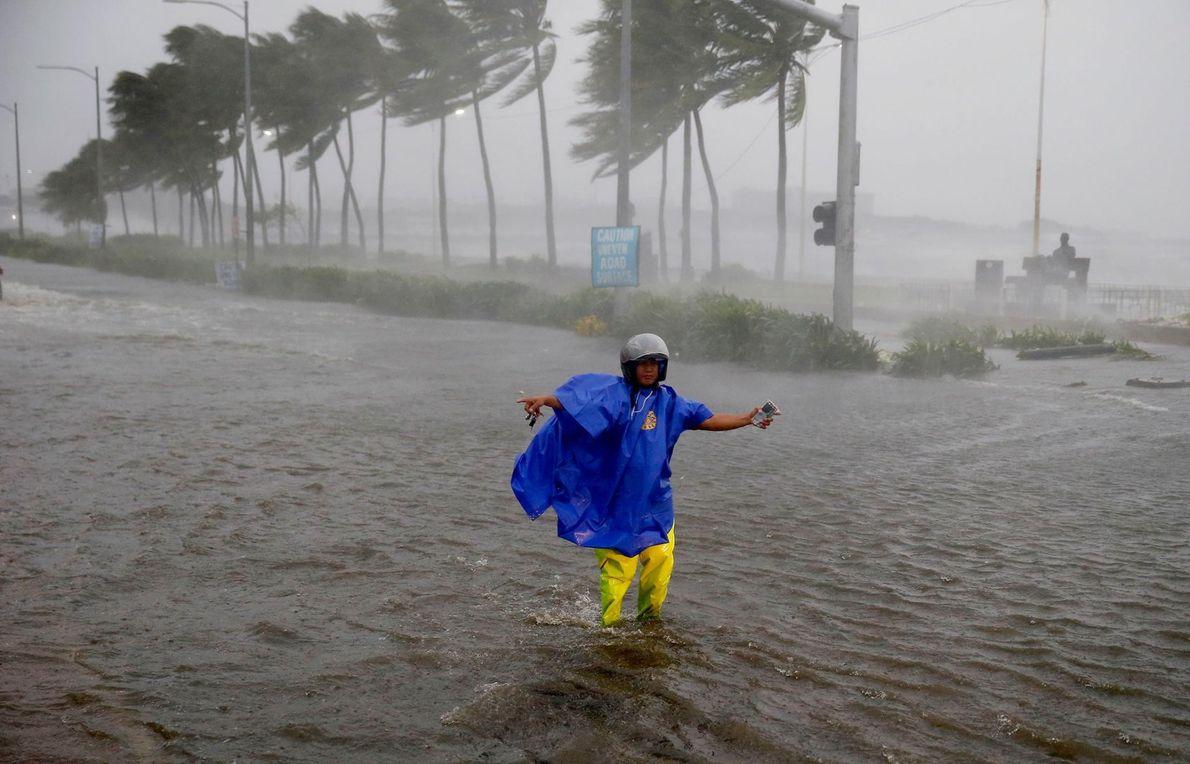 Un homme fait la circulation afin d'éviter une rue inondée suite à l'assaut du typhon Mangkhut ...