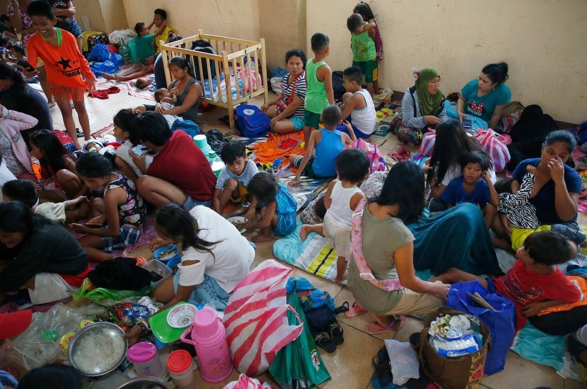Des habitants du quartier côtier de Baseco, aux Philippines, cherchent un refuge provisoire dans ce centre ...