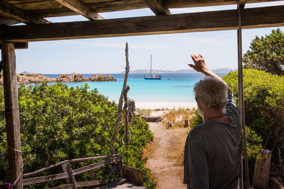 Morandi salue un bateau qui passe au loin depuis son porche. Bien que la plage ait ...